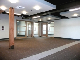 """With a floor-to-floor height of approximately 9 feet the original office felt dark and oppressive. To bring a sense of height, light and openness to this level, the acoustical ceiling tiles were removed, the existing structure and the new mechanical systems were painted a chocolate brown, and """"clouds"""" were added to both reflect light down and provide interest. Additionally, solid doors were replaced with glass doors and large sidelights were added; both allow daylight to filter in to the space and peak-a-boo views to the landscape outside. Photo courtesy MSGS Architects."""